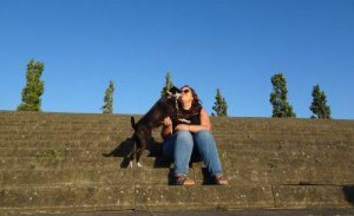 Vrouw zit met hond op de trap te knuffelen