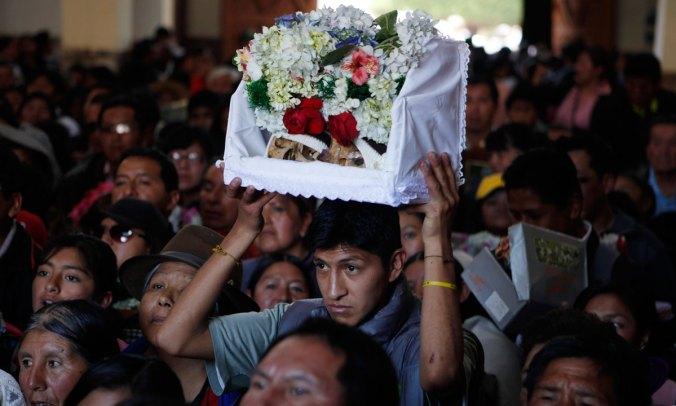 Family members carry ñatitas into a church