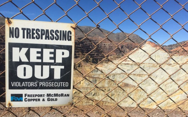 """A """"no trespassing"""" sign gets the message across, attached to barbed-wire fencing outside of the now-defunct Copper Queen Mine. The mine propelled Bisbee to regional economic prosperity, until its closing in 1985. (Photo by Diego Mendoza-Moyers/Cronkite news)"""