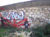 """Muro con un enigmático grafiti conmemorativo (con firma sin documentar en la zona) con un sol naciente flanqueado por dos samurais, con la leyenda """"Abu"""" y """"dedicado a mi abuelo"""", en la trasera de los barracones (foto AGR, nov. 2006)"""