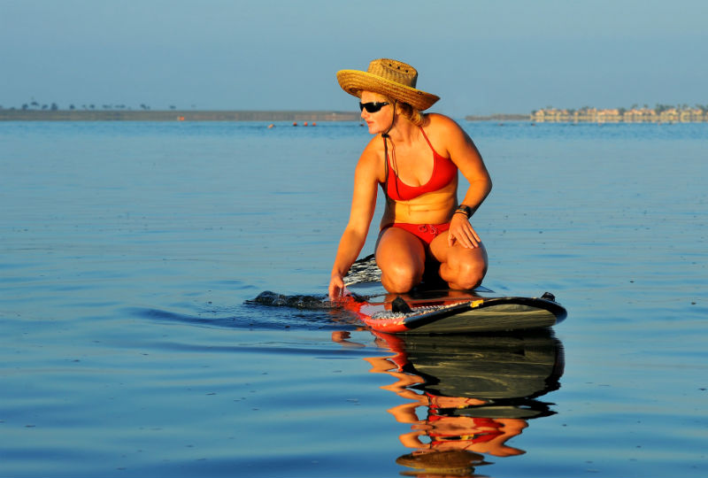 girl on bikini kneeling on padddleboard