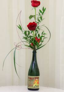 red roses and florist greens in a vintage wine glass, perfect for any wine lover