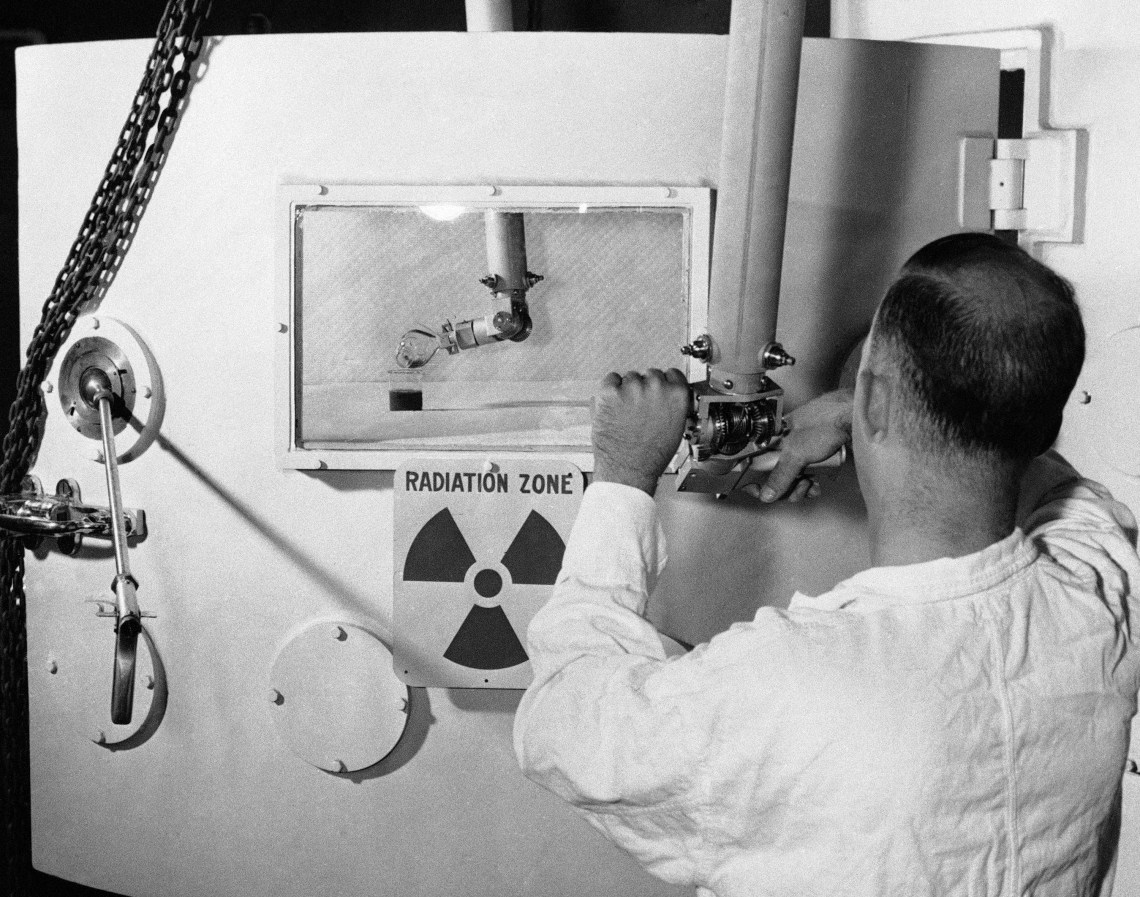 "A man works a lever in front of a sign that reads ""Radiation Zone"""