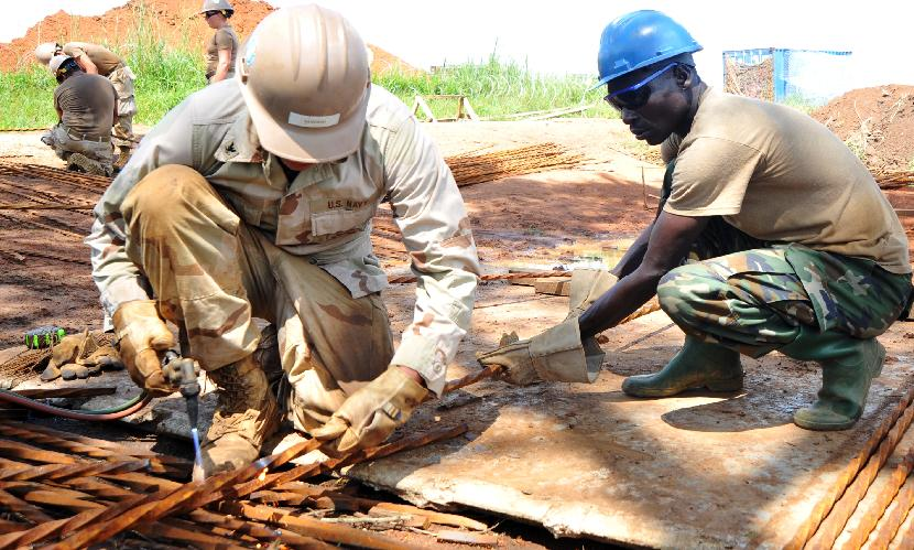 AROMO, Uganda - Seaman Apprentice John Sanders, Naval Mobile Construction Battalion 3, and Uganda Peoples' Defence Force Corporal Ongora Bonny begin constructing the foundation of a bridge in Aromo, Uganda, October 10, 2009. The bridge, scheduled to be completed in January 2010, will benefit local residents by improving their transportation ability. (Photo by Staff Sergeant Ronald Lafosse, CJTF-HOA)