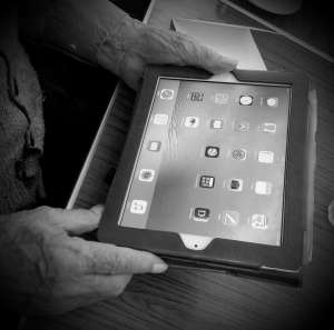 Elderly person using and iPad to illustrate his capacity