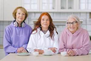 happy elderly women sitting at table with coffee in a retirement home