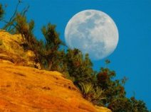 Full moon rising over red cliffs symbolize the Sedona full moon inspiration circles and connecting with its energy.