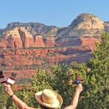 Woman with arms lifted up looking red cliffs; symbolizes Sedona sunrise and sunset ceremony during this fall time of change season