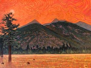 Orange hot sky of San Francisco Peaks with dried out grasslands below.