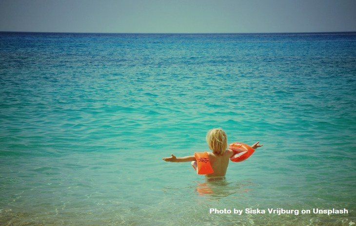 A little boy is standing in the ocean with arms extended and wide open. He's wearing orange floaters on his arms.