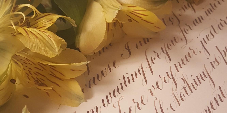 Fresh flowers resting on handlettered calligraphy