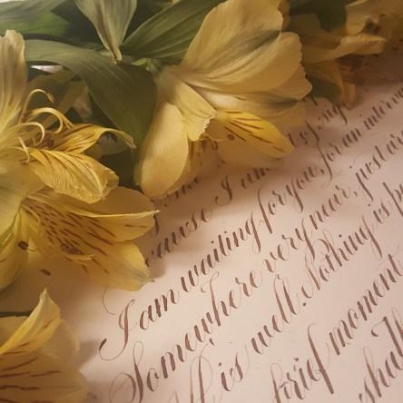Fresh flowers resting on handlettered calligraphy