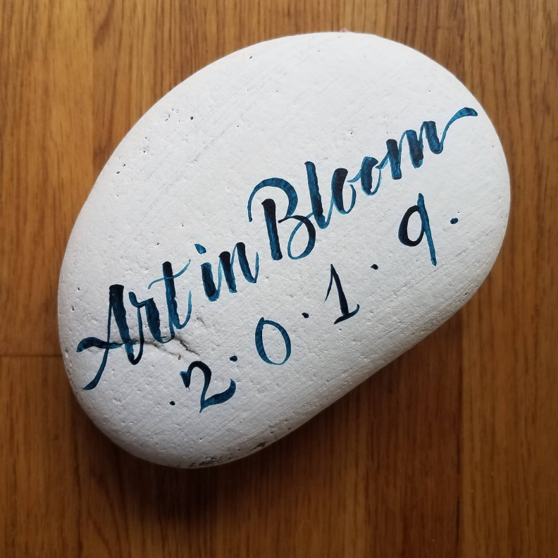 Brush lettered calligraphy door prize on river rock