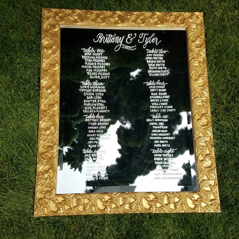 Wedding seating chart on a large gold mirror