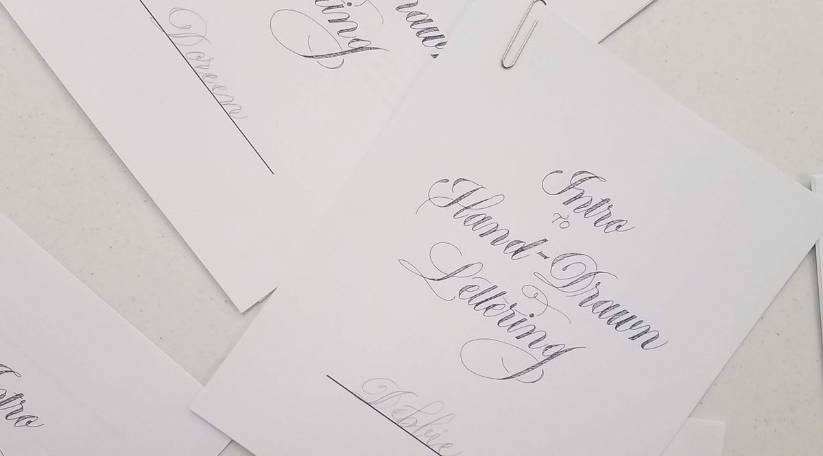 """A set of instructional packets printed on white paper and arranged on a white table. The title, """"Into to Hand Drawn Lettering"""", is written in black ink using a cursive script."""