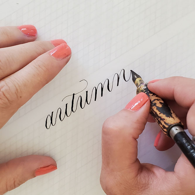 """a calligrapher's hand writing the word, """"autumn"""" in cursive using a pointed pen and brown ink."""