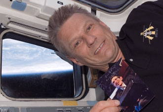 Astronaut Piers Sellers holds a photo of Dr. Stephen Hawking on board Discovery during the STS-121 mission in July 2006. Credit: NASA.