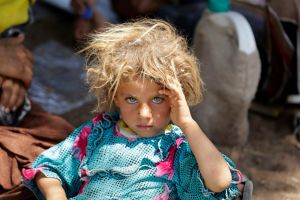 A girl from the minority Yazidi sect, fleeing the violence in the Iraqi town of Sinjar, rests at the Iraqi-Syrian border crossing in Fishkhabour, Dohuk province August 13, 2014. REUTERS/Youssef Boudlal (IRAQ - Tags: CIVIL UNREST POLITICS TPX IMAGES OF THE DAY) - RTR42BT8