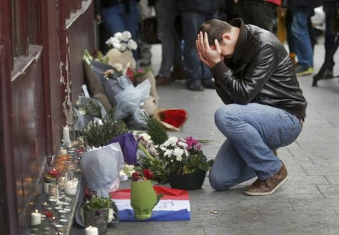 A man pays his respect outside the Le Carillon restaurant the morning after a series of deadly attacks in Paris , November 14, 2015. REUTERS/Christian Hartmann