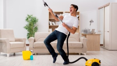 This is a man enjoying his time cleaning his apartment.