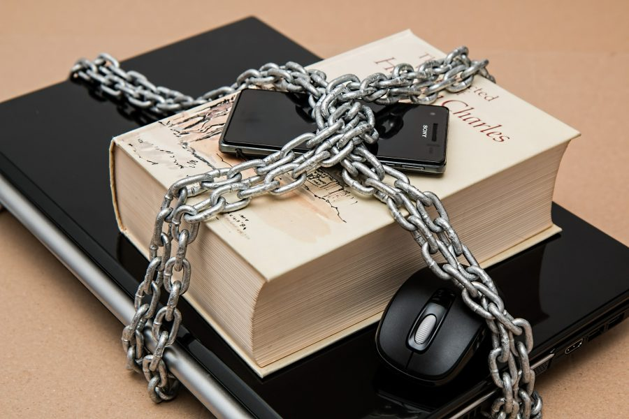 Magic Limitations are Essential for a Powerful System cover image - laptop, book, and phone all wrapped in chains