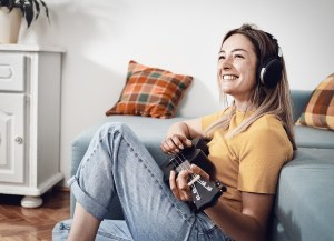 Woman playing ukulele at home. Domestic lifestyle. Woman relaxing at home