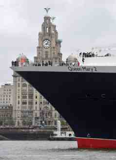 Cunard 175th celebrations on the River Mersey, Liverpool pictured The Three Queens cruise liner Queen Mary 2 pulls up alongside the Liver buildings on the river. Photo by Colin Lane