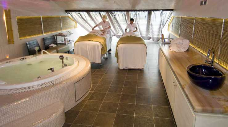 Massage therapists administer a couple's bamboo massage on Carnival Magic's Cloud 9 Spa. The two-level facility also includes a full gymnasium, thermal suite and spa accommodations with special access and privileges. Photo by Andy Newman/Carnival Cruise Lines