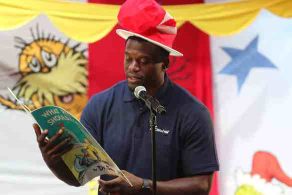"""New Orleans Saints tight end Benjamin Watson reads a Dr. Seuss Book to a group of children during the """"Dr. Seuss at Sea"""" on the Carnival Triumph cruise liner at the Port of New Orleans on Saturday, July 21, 2018.  (Photo by Peter G. Forest)"""