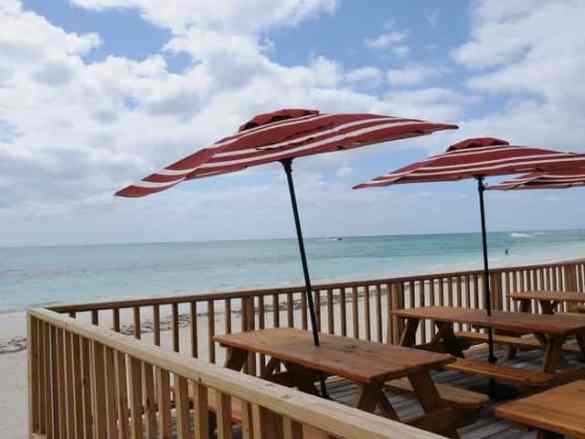 Tables overlooking the large beach area at the Bahamas Adventures Beach Club located in Freeport, Bahamas.