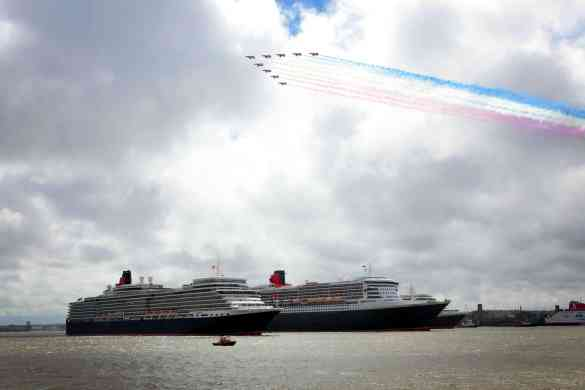 Crowds flock to the Liverpool waterfront to watch the three queens, Queen Elizabeth, Queen Mary 2 and Queen Victoria perform a river dance together during  Cunard's 175 years celebrations as the Red Arrows fly overhead.  VT