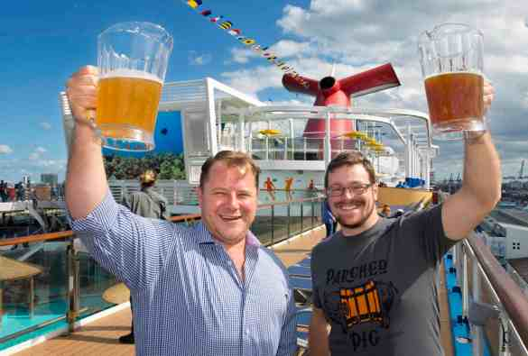 At a Sunday, Jan. 7. 2018, beer-tasting event aboard Carnival Vista at PortMiami, Carnival Cruise Line's Vice President of Beverage Operations Edward Allen, left, and Brewmaster Colin  Presby, right, hoist pitchers filled with craft beers that will be featured in the Smokehouse Brewhouse restaurant on the new Carnival Horizon set to debut this spring.  In addition to craft beers created by Presby, Smokehouse Brewhouse will offer barbecue favorites created by Food Network star and Carnival partner Guy Fieri. Photo by Andy Newman/Carnival Cruise Line