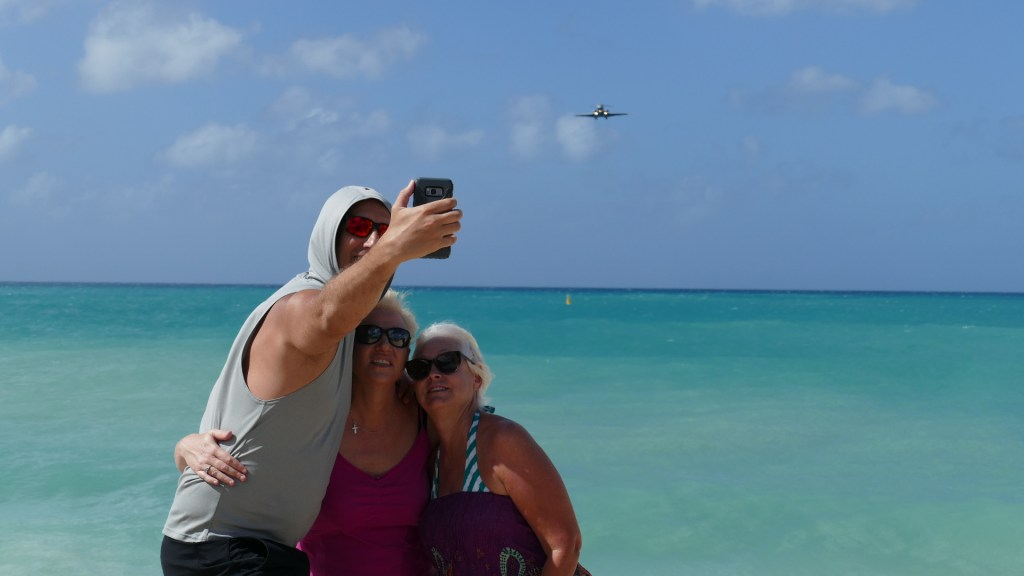 Tourists taking a selfie with the airplane