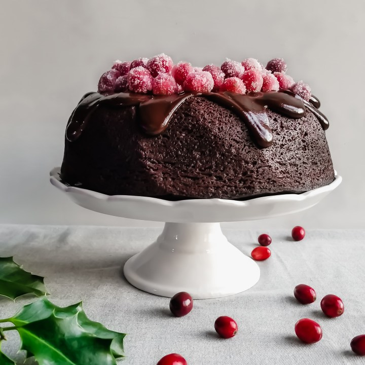 Vegan Cranberry Chocolate Fudge Cake with Ganache and Sugared Cranberries served on a white platter with holly and cranberries on the table