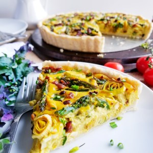 Asparagus, Leek and Tempeh Bacon Quiche in a tender Biscuit Crust sliced on a white plate