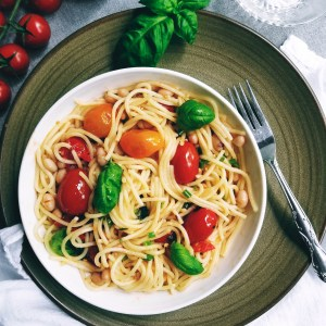 Plate with Cherry Tomato Pasta garnished with fresh basil leaves
