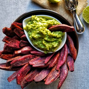 crispy purple sweet potato wedges in a black bowl with a second smaller white bowl filled with guacamole