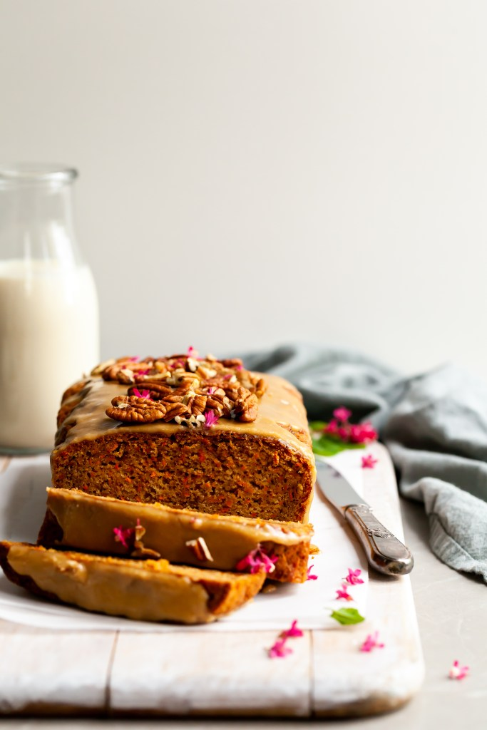 Vegan Carrot Spice Loaf with Maple Glaze with 2 slices cut and garnished with pink currant blossoms