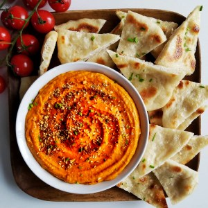 a swirl made in a white bowl of bright orange romesco sauce, served with naan triangles and fresh cherry tomatoes