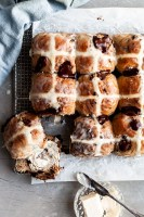Flatlay of hot cross buns on a cooling rack, with one having been cut in half and smeared with vegan butter