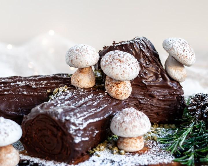 Vegan Chocolate Yule Log with Meringue Mushrooms served with candy snow and rosemary branches
