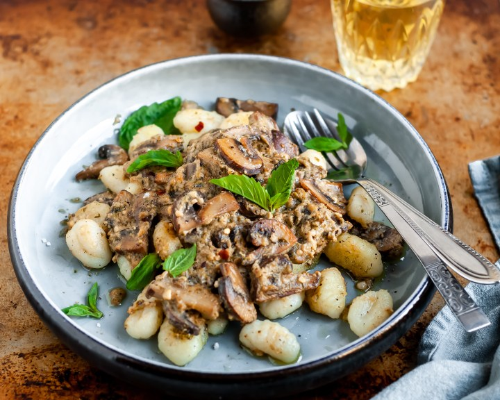 Plated Pan-Fried Gnocchi and Seared Mushrooms in a Cashew Butter Pesto garnished with fresh basil