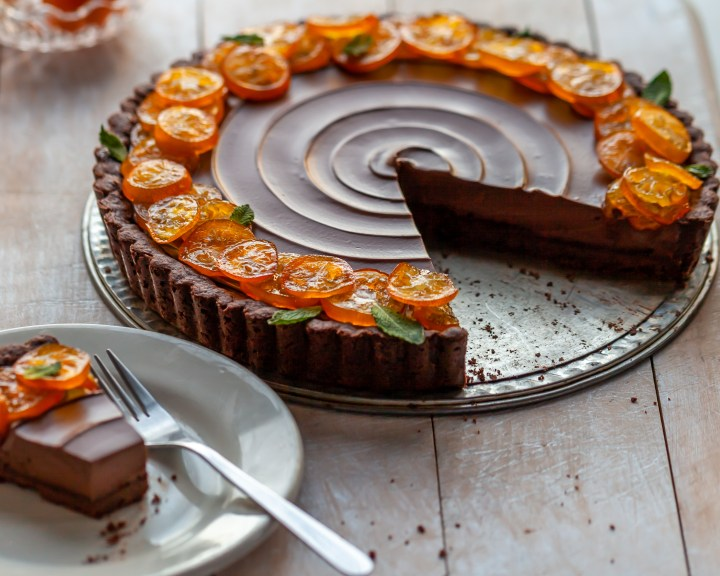 Vegan Chocolate Orange Tart with Candied Kumquats with 2 slices missing revealing the truffle like filling