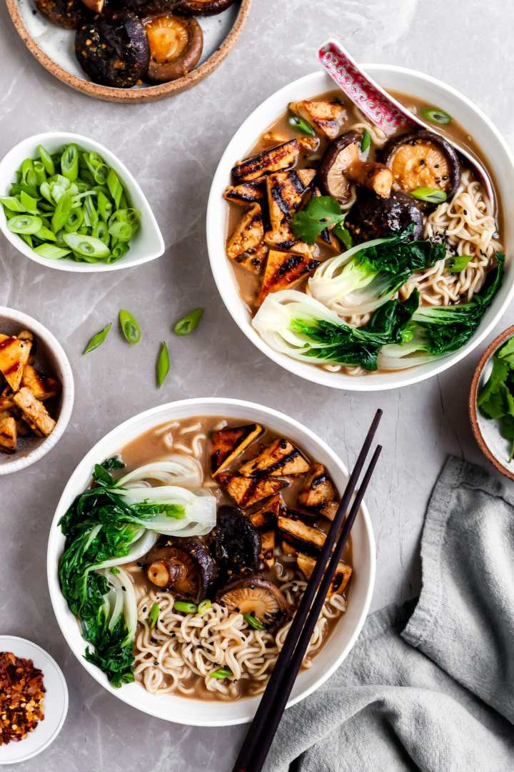 flatlay of 2 bowls of mushroom miso ramen and several bowls of garnishes
