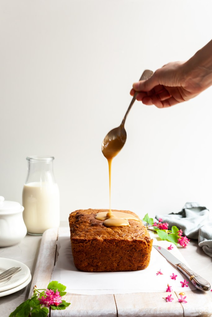 Vegan Carrot Spice Loaf with maple glaze being poured over the top