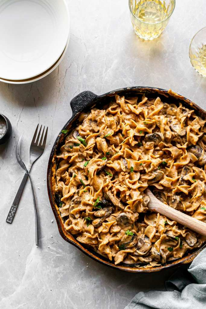 Mushroom Stroganoff in Cast Iron Skillet, ready to serve in white bowls