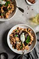 Mushroom Stroganoff served in white bowls, arnished with almond ricotta and parsley