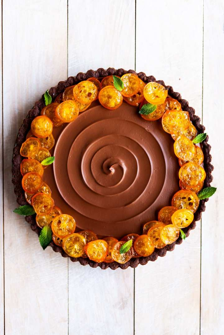 Vegan Chocolate Orange Tart with Candied Kumquats unsliced on a white wood background