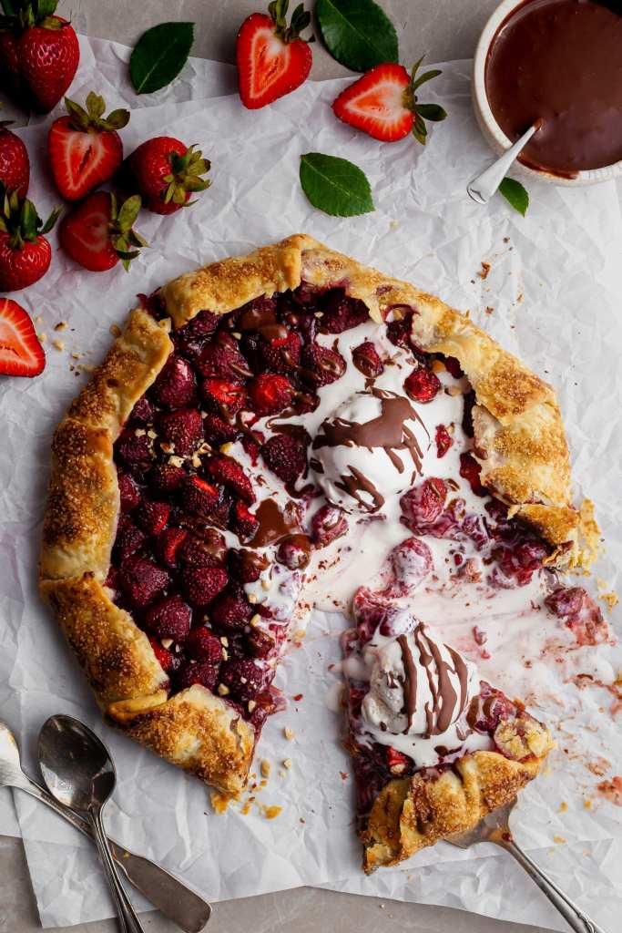 A second slice being served from a warm Fresh Strawberry Galette covered in melting vegan vanilla ice cream