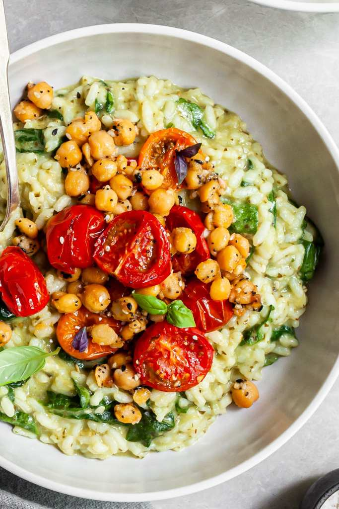 Close up view of a bowl of pesto risotto topped with roasted tomatoes and chickpeas